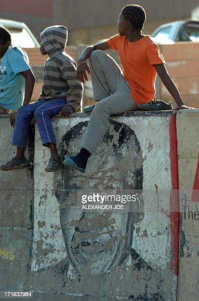 Children sit on a wall with an old painting of Nelson Mandela on a street of Alexandra township on June 27, 2013. Mandela is spending his 20 day in...