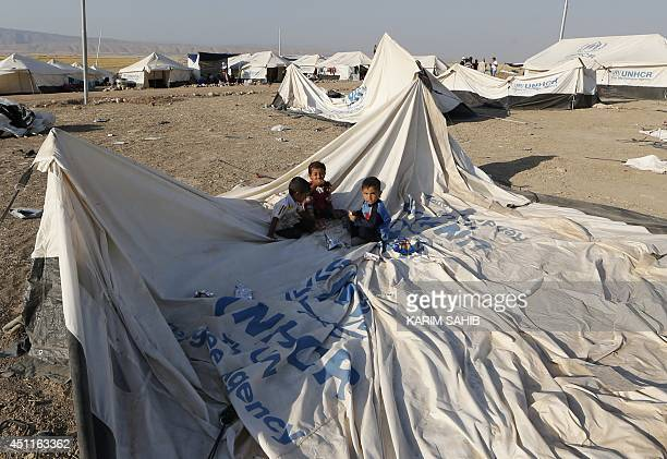 Children sit on disassembled tent at a camp for displaced Iraqi Shiite Turkmen who fled their town of Tal Afar, in Shikhan, in Kurdistan's Dohuk...