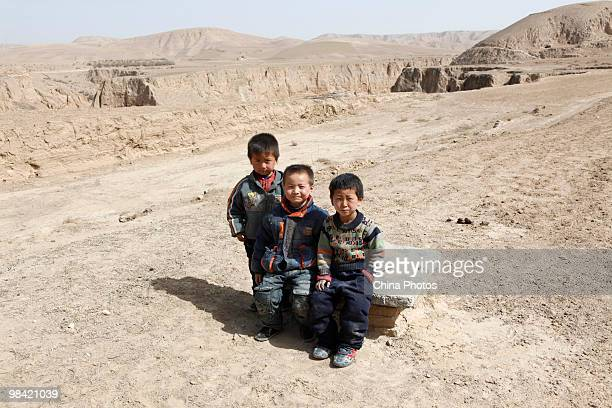 Children sit on the cover of a cistern on March 12 2010 in Xihaigu Tongxin County of Ningxia Hui Autonomous Region north China Xihaigu is the general...