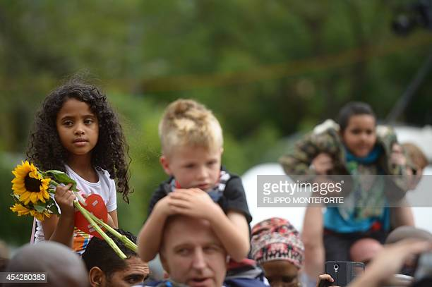 Children sit on their parent's shoulders as people gather outside South African former president Nelson Mandela's home in Houghton Johannesburg on...