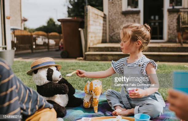 children sit outside and have a teddy bear's picnic - sibling stock pictures, royalty-free photos & images