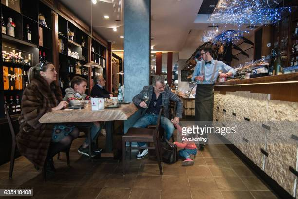 Children sit with their parents for lunch at a table in the Antonio Ferrari restaurant on February 15, 2017 in Padova, Italy. The restaurant offers a...