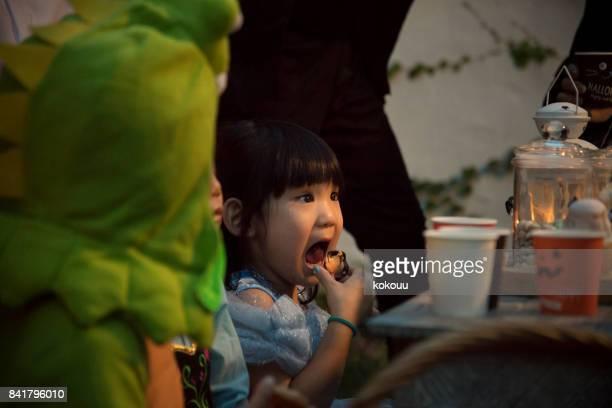 座っているとカップケーキを食べる子供たち。