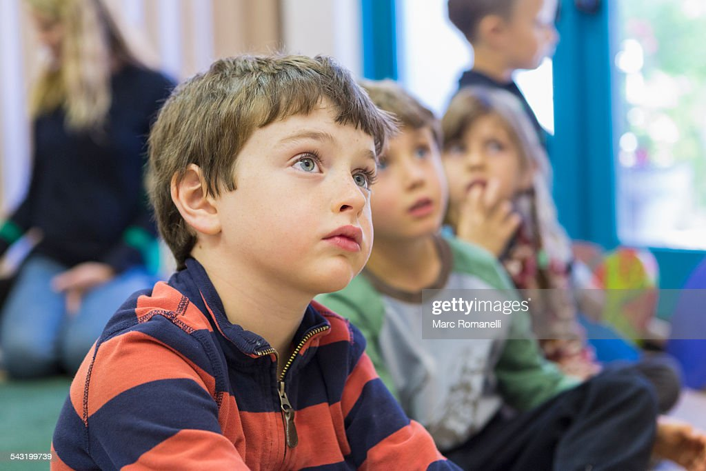 Children sitting and listening in classroom : Stock Photo