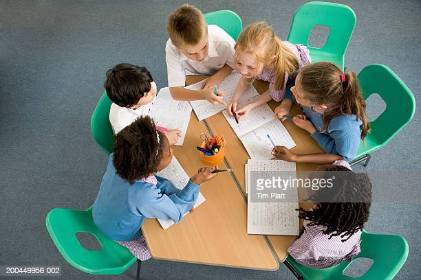 Children (7-12) sitting around table, having discussion, elevated view