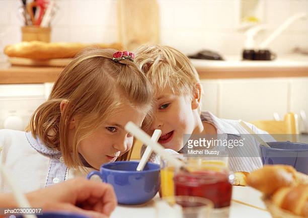 Children sitting at table leaning heads together, head and shoulders, cups, jelly jar and adult hand blurred in foreground
