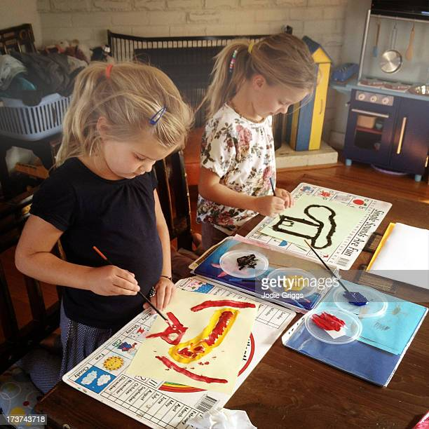 Children sitting at table painting pictures