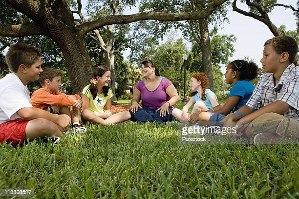 Children sitting in a circle on the grass with their teacher at a park