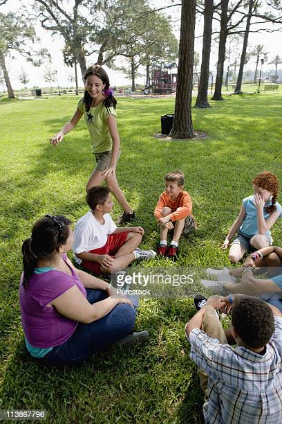Children sitting in a circle on the grass with their teacher while a girl walks around them