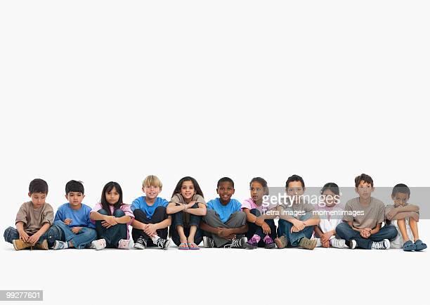 children sitting in a row - 人種や民族 ストックフォトと画像