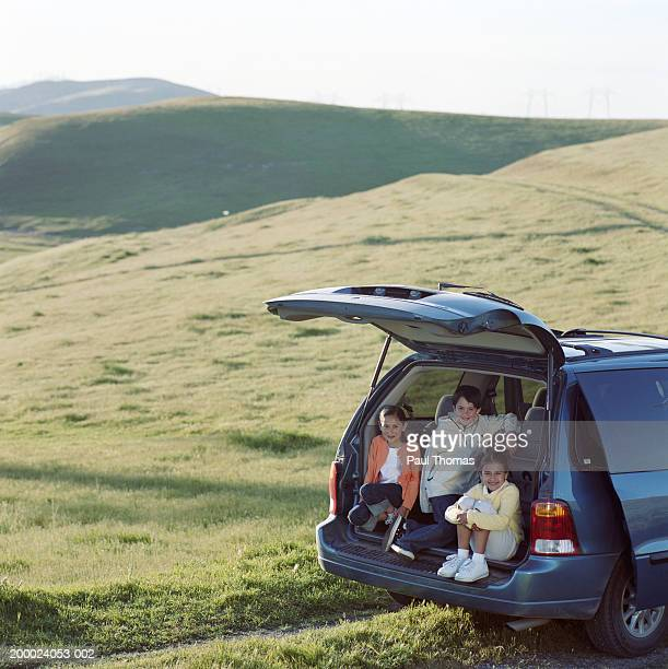 Children (5-10) sitting in back of open minivan parked in field