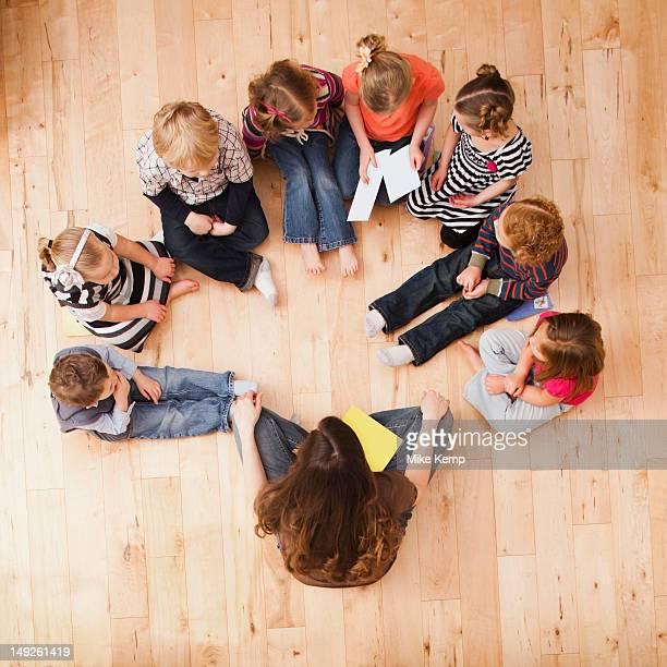 Children (2-3, 4-5) sitting in circle around teacher, directly above