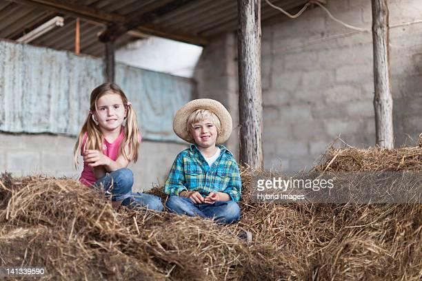 Kinder sitzen im Heuhaufen in stabiler