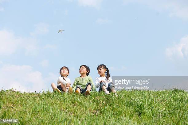 Children sitting in park and looking at flying paper airplane