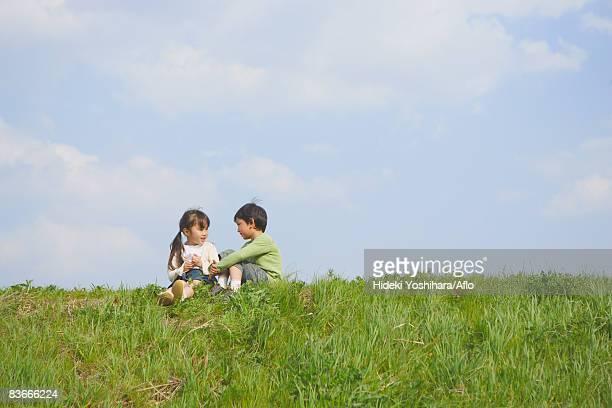 Children sitting in park together