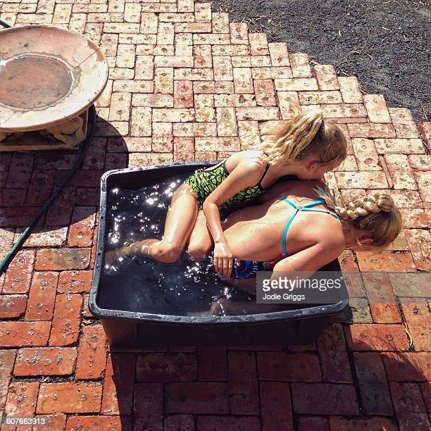 Children sitting in small tub of water on hot day
