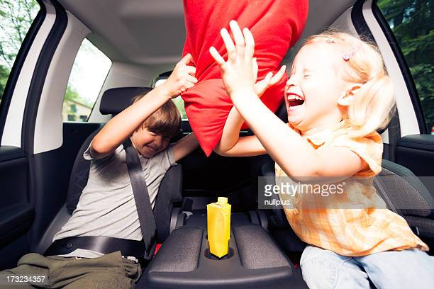 children sitting in the car, having a pillow fight