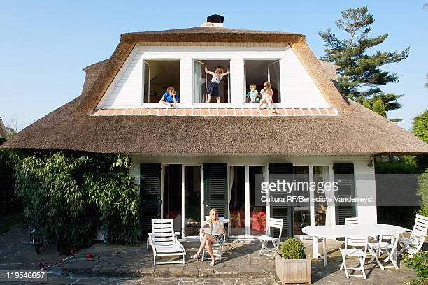 children sitting in windows of home - belgium stock pictures, royalty-free photos & images