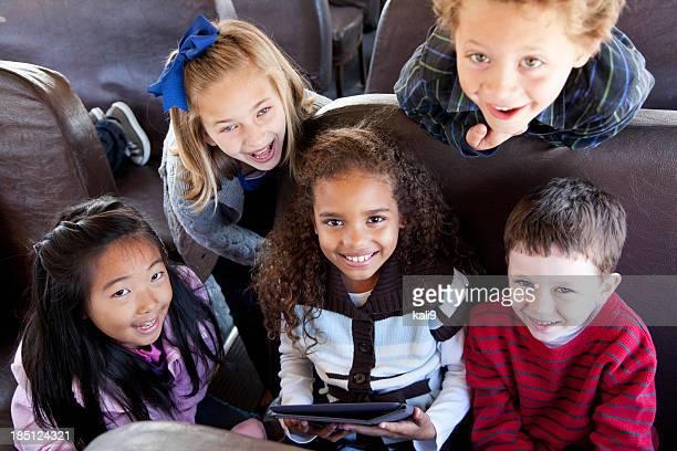 Sala de estar dentro de los niños de escuela con tableta digital autobús