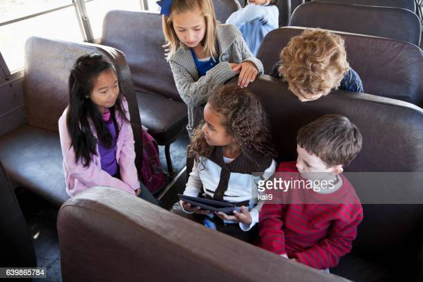 Children sitting inside school bus with digital tablet