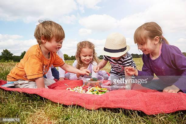 Children sitting on a blanket choosing sweets
