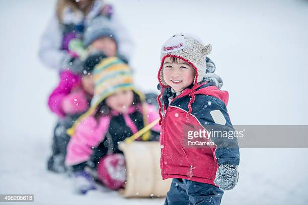 Children Sitting on a Sled on a Winter Day