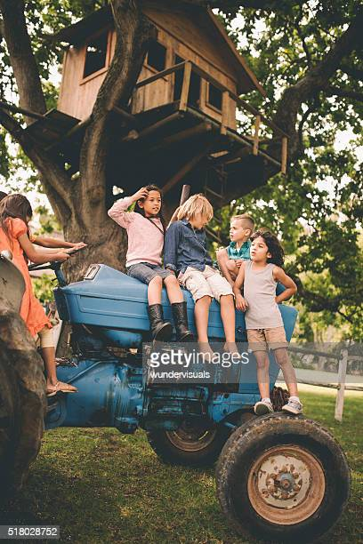Children sitting on a tractor under big tree with treehouse