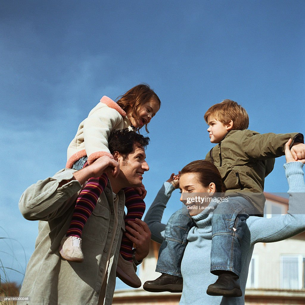 Children sitting on adults' shoulders : Stockfoto