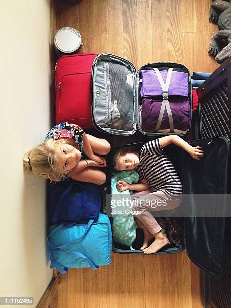 Children sitting on and inside packed suitcases