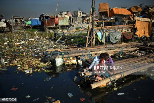 Children sitting on bamboos near their house on the waters of Manila bay on April 26 2017 in Manila Philippines Metro Manila has been facing an...