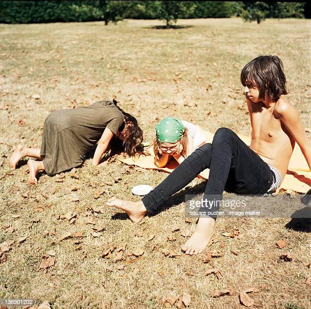 3 children sitting on burned grass