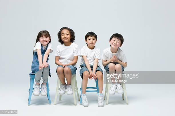 Children sitting on chairs, studio shot