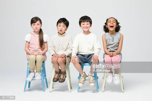 Children sitting on chairs, studio shot, portrait