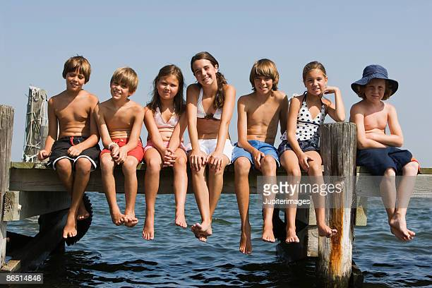 children sitting on dock - teen boy barefoot stock photos and pictures