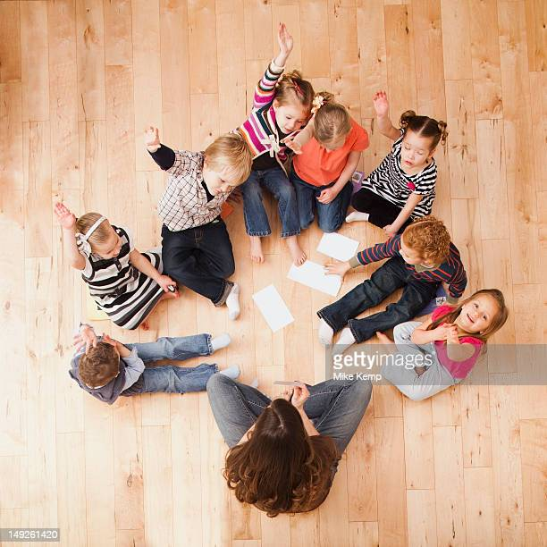 Children (2-3, 4-5) sitting on floor and raising hands, directly above