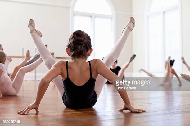 Children sitting on floor practicing ballet in ballet school