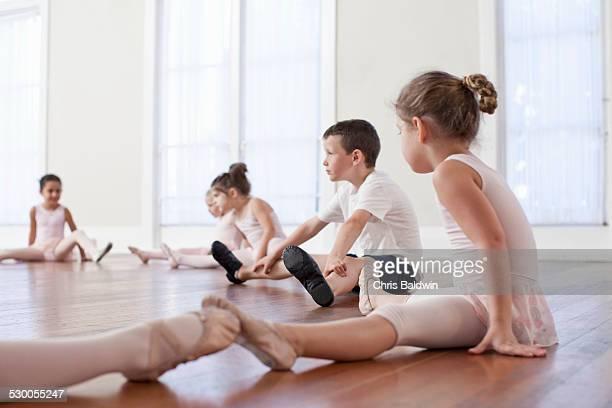 Children sitting on floor practicing ballet position in ballet school
