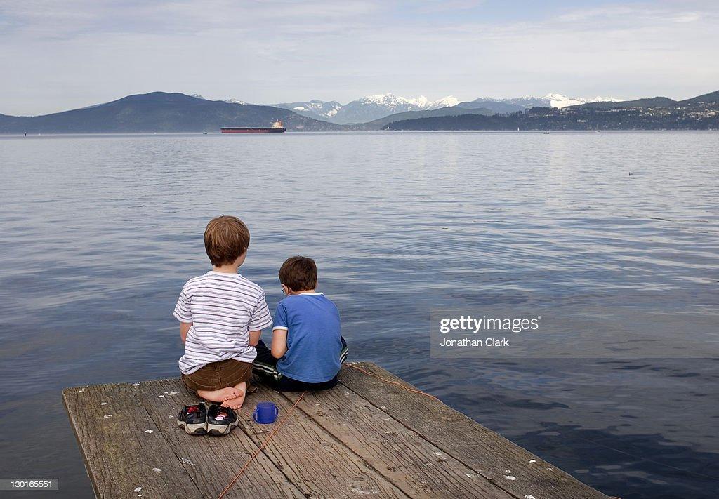 Children sitting on  pier. : Stock Photo