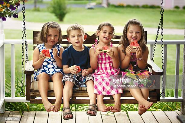 Children sitting on porch swing with watermelon