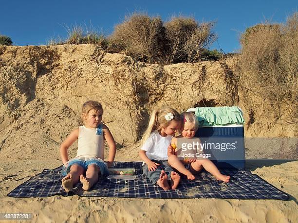 Children sitting on rug at the beach having picnic