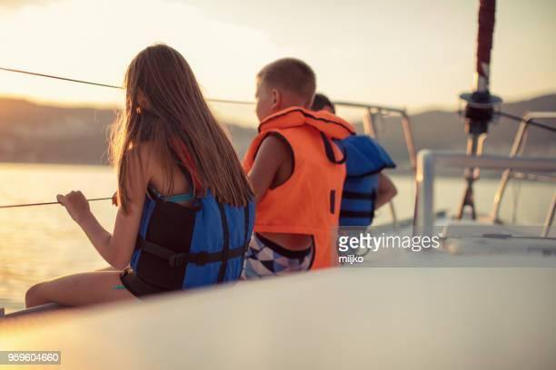 enfants assis sur le pont du voilier alors qu'il naviguait - navigation de plaisance photos et images de collection