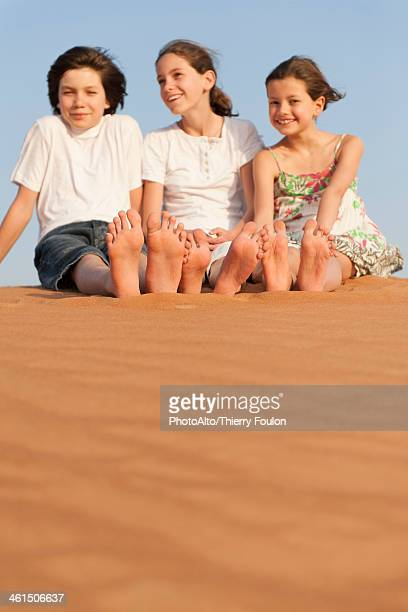Children sitting on sand dune