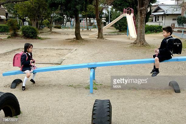 Children sitting on seesaw
