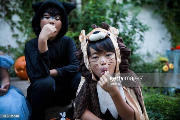 children sitting outside and eating candy. - dark panthera stock pictures, royalty-free photos & images