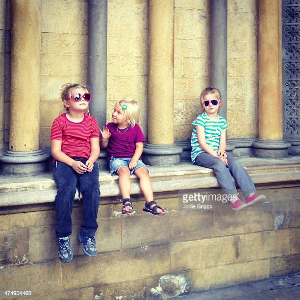 Children sitting outside on old stone building