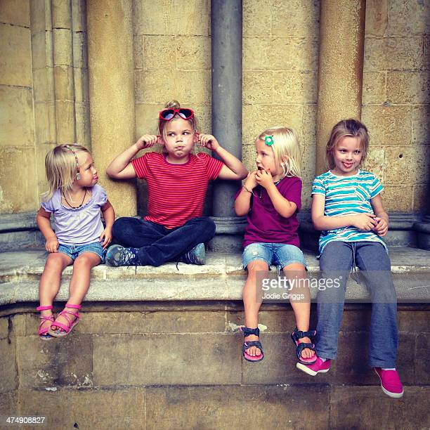 Children sitting outside pulling silly faces