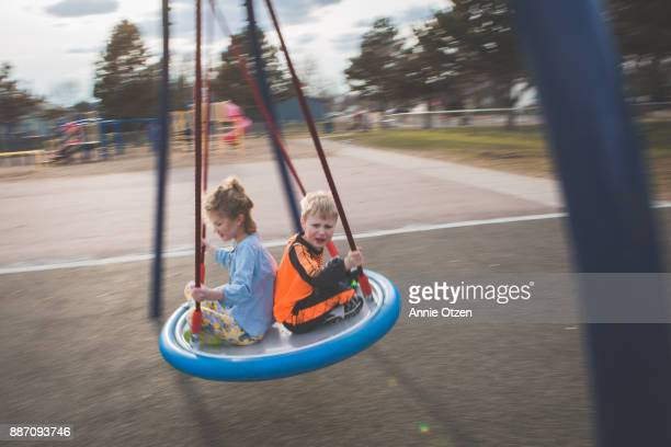 Children sitting together on a round swing.