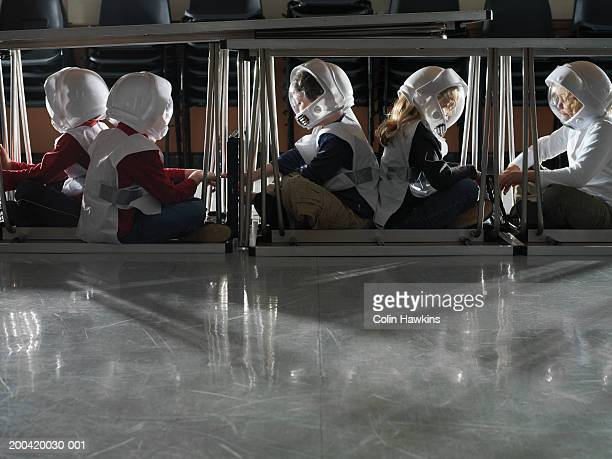 Children (5-7) sitting under tables in spacemen costumes, side view