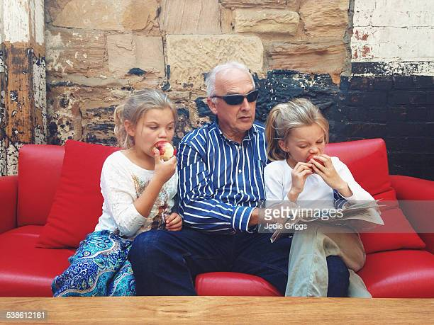Children sitting with grandfather reading paper