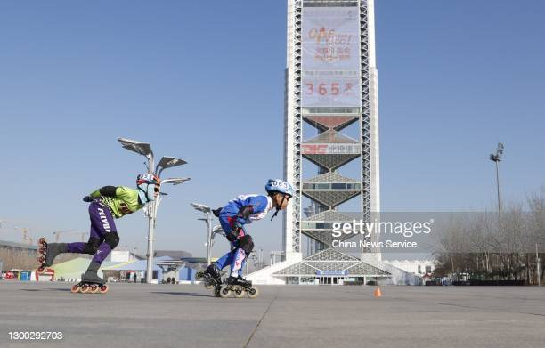 Children skate past a countdown clock for the Beijing 2022 Olympic Winter Games at Beijing Olympic Park on February 4, 2021 in Beijing, China. China...